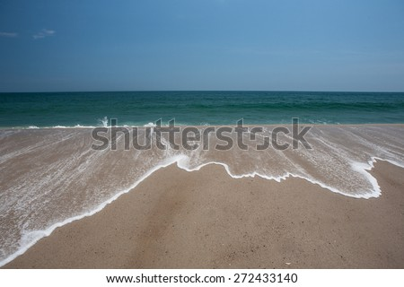 The cold Atlantic Ocean washes against the sandy peninsula of Cape Cod, Massachusetts. The sea continually erodes shorelines, moving significant amounts of sand every season. - stock photo