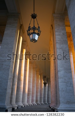 The Colonnade located in the front of the St. Peter's Basilica (Basilica di San Pietro) in Vatican on the sunset sun. The columns are surrounding the famous Saint Peter's Square (Piazza San Pietro)