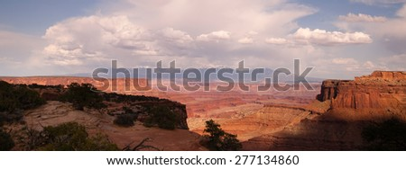 The Colorado River has cut out a massive canyon below and island in the sky - stock photo