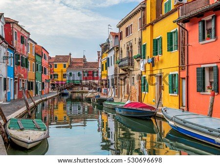 The colored houses on the shore of a channel on a sunny day - Burano, Venice, Italy