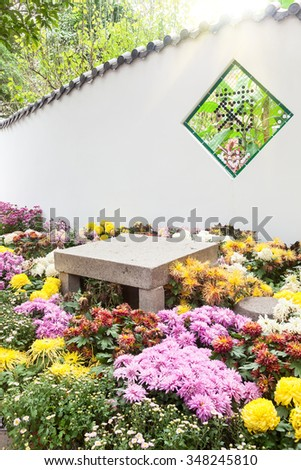 "The Colorful chrysanthemums flowerbed with the stone table and seat  in a garden,the symbol on window means ""chrysanthemum"" in chinese"