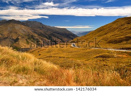 The colorful countryside on the drive through the Crown Ranges, en route to Queenstown in the south island of New Zealand. - stock photo