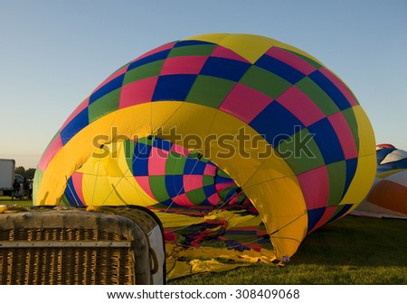The colorful envelope of a hot-air balloon being inflated on the ground. - stock photo