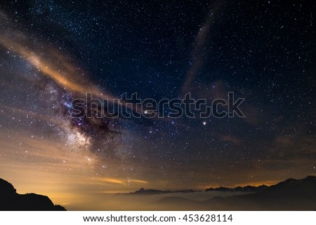 The colorful glowing core of the Milky Way and the starry sky captured at high altitude in summertime on the Italian Alps, Torino Province. Mars and Saturn glowing mid frame. - stock photo