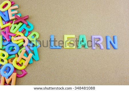 """The colorful word """"LEARN"""" next to a pile of other letters over the brown board surface composition. - stock photo"""