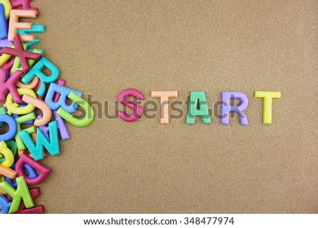 """The colorful word """"START"""" next to a pile of other letters over the brown board surface composition. - stock photo"""