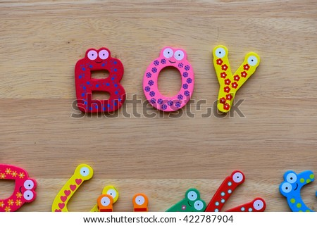 """The colorful words """"boy"""" made with wooden letters next to a pile of other letters over old wooden board. - stock photo"""