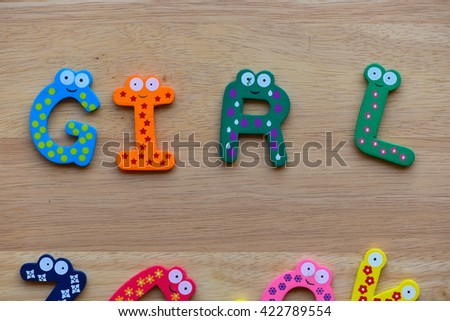 """The colorful words """" Girl """" made with wooden letters next to a pile of other letters over  wooden board. - stock photo"""