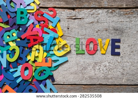 "The colorful words ""LOVE"" made with wooden letters next to a pile of other letters over old wooden board. - stock photo"