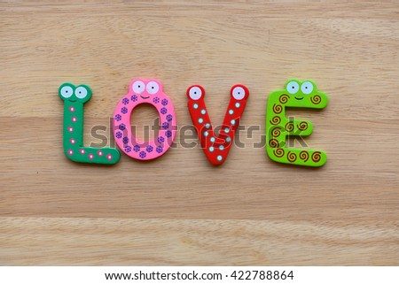 """The colorful words """" LOVE """" made with wooden letters next to a pile of other letters over  wooden board. - stock photo"""