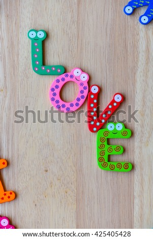 """The colorful words """"love"""" made with wooden letters next to a pile of other letters over wooden board. - stock photo"""