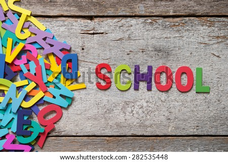 "The colorful words ""SCHOOL"" made with wooden letters next to a pile of other letters over old wooden board. - stock photo"