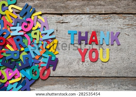 "The colorful words ""THANK YOU"" made with wooden letters next to a pile of other letters over old wooden board. - stock photo"