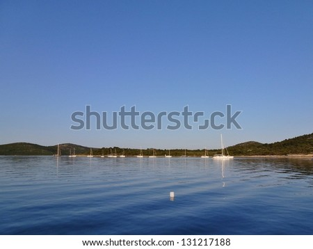 The colors of a rocky coast in a bay in the Adriatic sea of Croatia with a white floating fender - stock photo