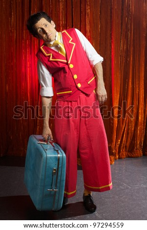 The comedian with  suitcase on stage in theater - stock photo