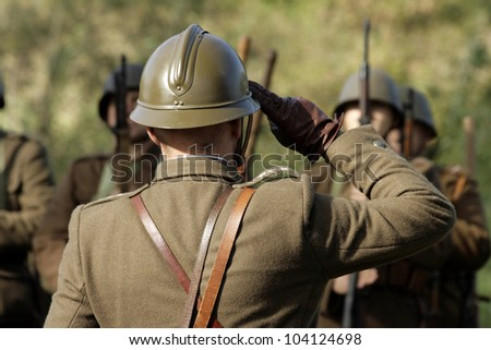 The commander is saluting before the company of soldiers - stock photo