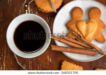 The composition of ginger biscuits, cup of coffee and a plate of cinnamon
