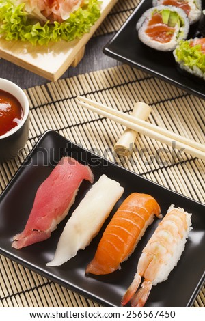 The composition of nigiri sushi with tuna, salmon, shrimp, butterfish on rice
