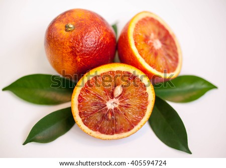 The composition of red orange with green leaves on a light background