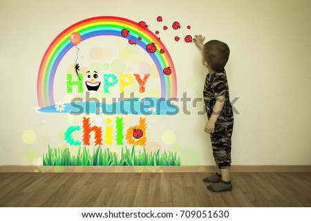 The concept of a happy childhood. The grass with ladybirds and flowers. The little boy draws on the wall. Fantasy for children.