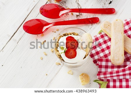 The concept of a healthy breakfast. Crispy homemade granola with nuts and berries with fresh strawberries in a glass portioned cups on a white background are served for breakfast. selective focus
