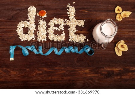 The concept of a healthy diet; the word diet is lined with oat flakes on a dark wooden background, next to the yogurt and dried fruits