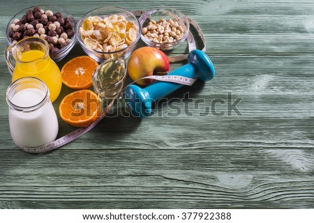 The concept of a healthy lifestyle. Cornflakes, orange juice, yogurt, nuts, honey, tangerines, apple, dumbbell  and measuring tape on rustic wooden table.