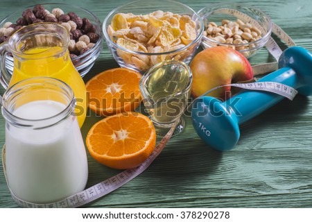 The concept of a healthy lifestyle. Cornflakes, orange juice, yogurt, nuts, honey, tangerines, apple, dumbbell  and measuring tape on rustic wooden table.Cereals and fruit - diet and breakfast - stock photo