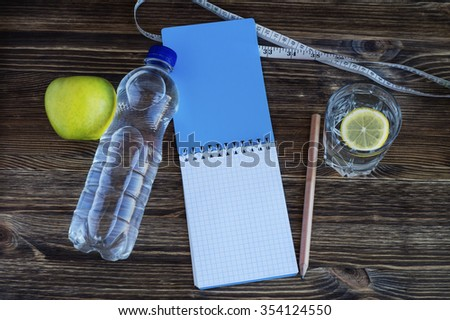 The concept of a healthy lifestyle. Workout and fitness dieting copy space diary. Apple, water and measuring tape on a wooden table. - stock photo