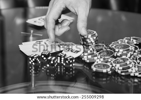 The concept of card games. Man playing poker at the poker table. Playing chip cards and whiskey on the table - stock photo