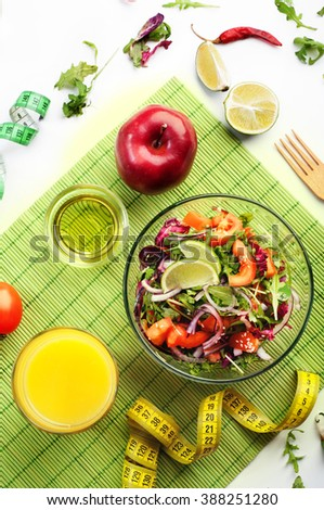 The concept of dietetic vegetarian food. Salad with arugula, tomatoes and onions, close to orange juice, apple and measuring tape, which symbolizes the reduction in volume of the body.