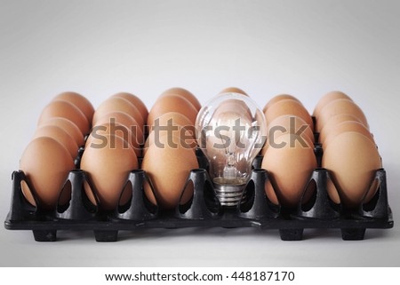 The concept of energy,Lamps and eggs in the egg tray. - stock photo