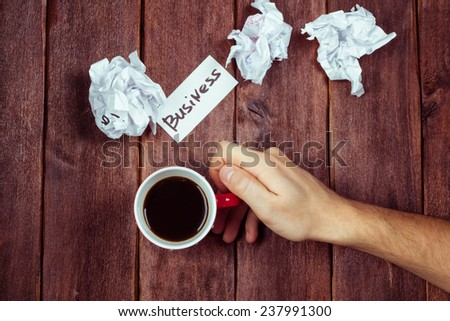 The concept of generating ideas, brainstorming, search solutions for business. Generating ideas for business. Man's hand with a cup of coffee and crumpled paper. - stock photo