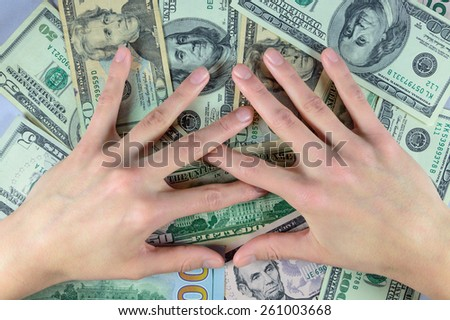 The concept of greed two hands on a pile of money dollars - stock photo