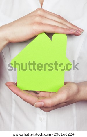 The concept of green building. Women's hands with a form of the house in  hands. Protection and security at home. Subject property, sustainability and protection of property. - stock photo