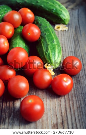 The concept of healthy eating with organic cucumber and cherry tomatoes on wooden table - stock photo