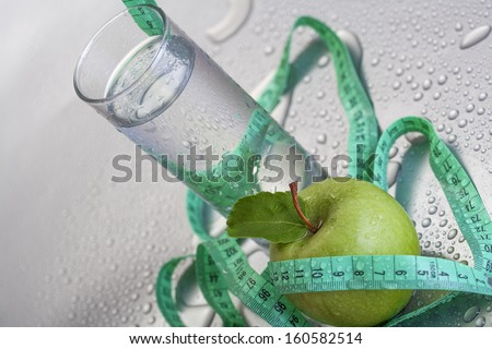 The concept of healthy living, apples and water with measuring tape - stock photo