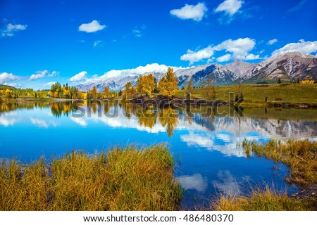 The concept of hiking. Bright shining autumn day in Canmore, near Banff National Park. Cumulus clouds are reflected in the lake