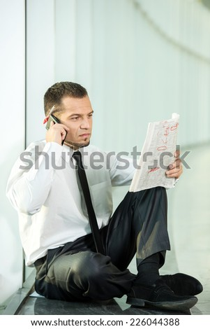 The concept of job search. A man is sitting with a newspaper and speaking by phone. - stock photo