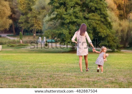 The concept of Mother's Day. Mother with little daughter walking in the park in the evening in summer, autumn, rear view.