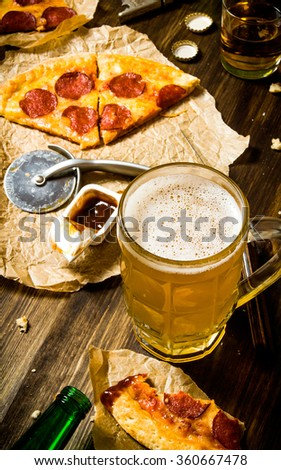 The concept of pizza with beer. Pepperoni pizza with beer on a wooden table. - stock photo