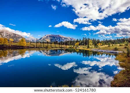 The concept of recreational tourism. Bright shining autumn day in Canmore, near Banff National Park. Majestic mountains and scenic cumulus clouds are reflected in the lake