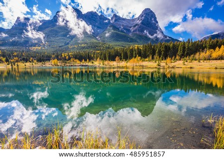 The concept of recreational tourism. Bright shining day in the Canadian Rockies. Canmore, near Banff National Park. Majestic mountains and red-orange trees