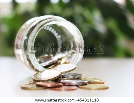 The concept of saving money . The money is scattered from a glass jar on the table. - stock photo