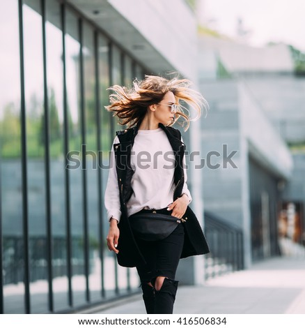 The concept of street fashion. Young beautiful model in the city. Beautiful blond woman wearing sunglasses. Dynamically young girl walks down the street.Hair fluttering in the wind. - stock photo