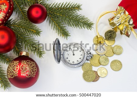 The concept of the New Year and Christmas.Two glass balls on fir-tree branches, watch and purse with coins.