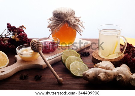 The concept of treating colds with natural resources, without tablets. Honey. lemon, ginger tea, cinnamon and anise stars, ginger root on a dark wooden background.