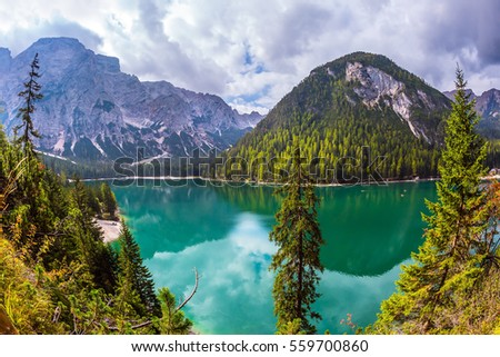 The concept of walking and eco-tourism. Green water reflects the surrounding forest and mountains. Magnificent lake Lago di Braies, South Tyrol, Italy