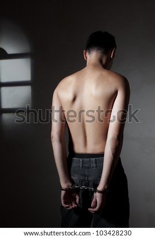 The concluded guy of the Asian appearance in handcuffs - stock photo
