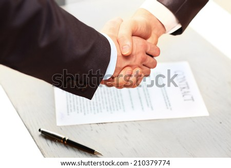 the conclusion of the contact. Closeup of a business hand shake between two colleagues - stock photo